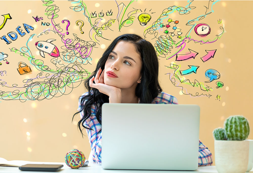 A woman is brainstorming in front of the computer